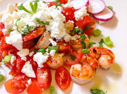 Sliced tomato with a sprinkle of feta and olive oil